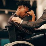 A man in a wheelchair holds his head in his hands.